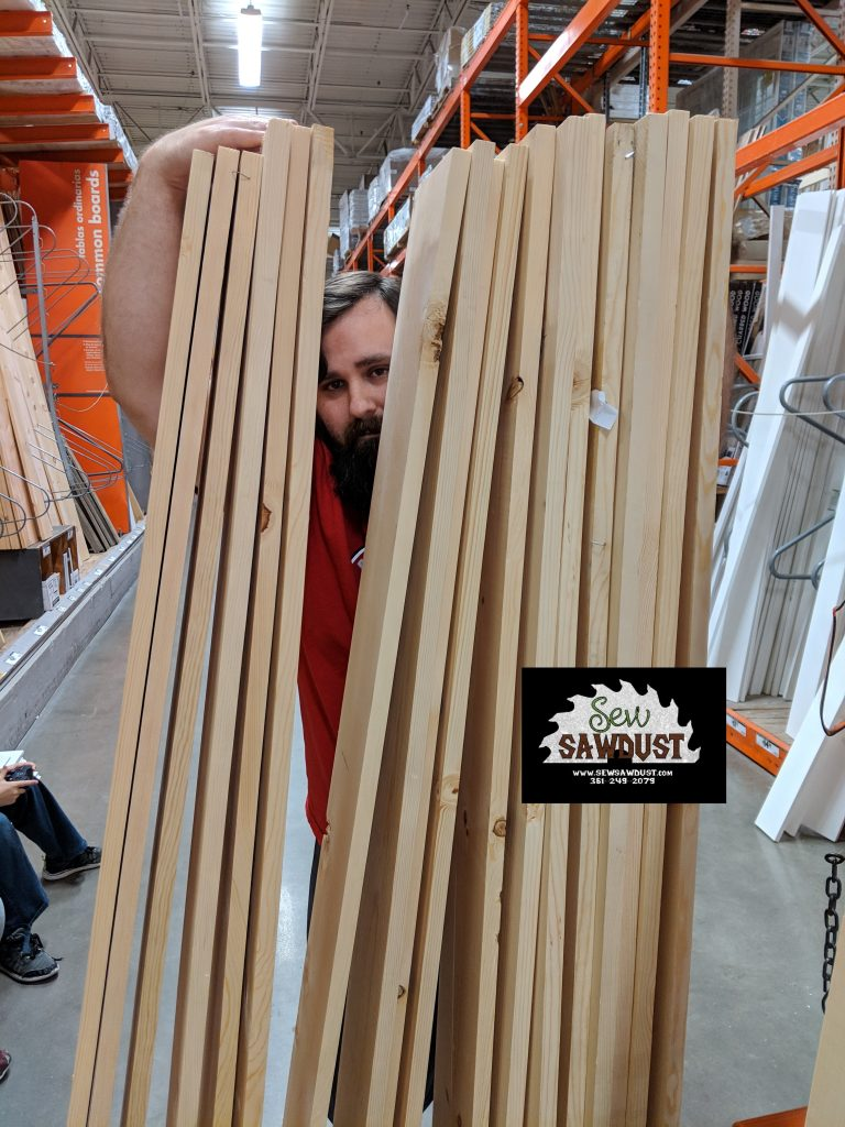 The husband of sew Sawdust owner Stephanie holding up the reject pile, while looking for good pieces to use.