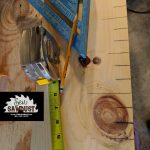 Measuring inches on a board to router out a growth chart, prep work being done by sew sawdust