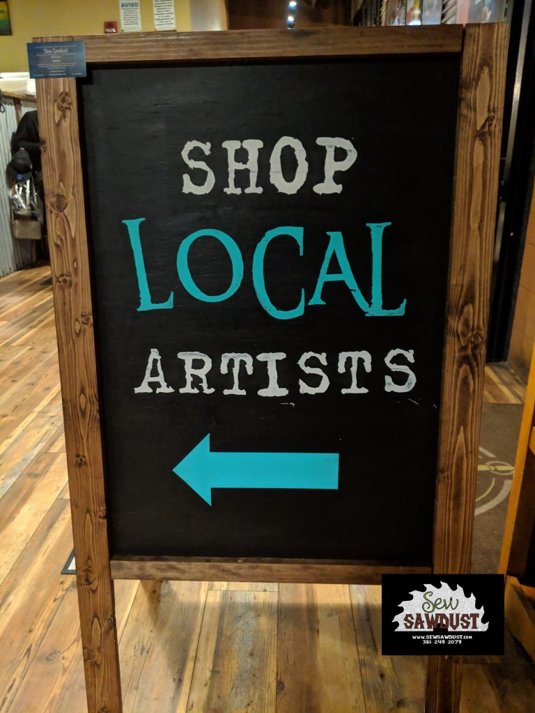 """An all wood custom made sandwich board with """"shop local artists"""" painted on. Made by Sew Sawdust."""